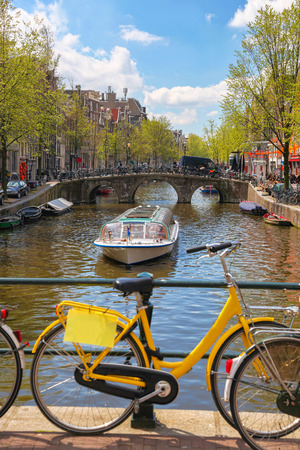 Amsterdam with  bicycle on the bridge against boat in  Holland photo