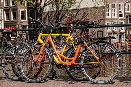 Amsterdam with bicycles on the bridge against canal in Holland photo