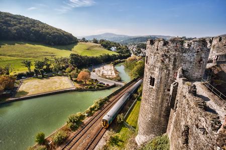 welsh flag: Famoso Conwy Castle in Galles con il treno, Regno Unito, serie di castelli Walesh