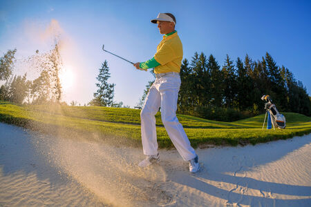 Man playing golf from bunker against sunset photo