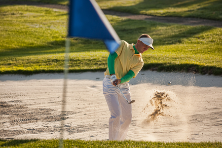 Man playing golf from bunker photo