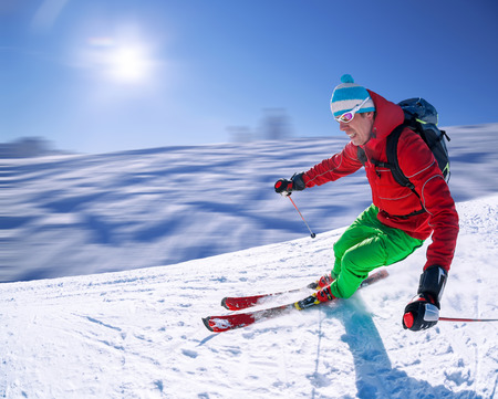Skier skiing downhill in high mountains against sunset photo