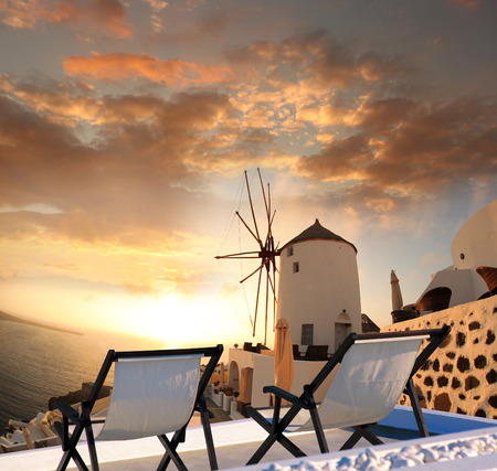 Windmill against colorful sunset in Santorini, Greece photo