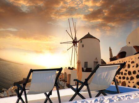 caldera: Windmill against colorful sunset in Santorini, Greece