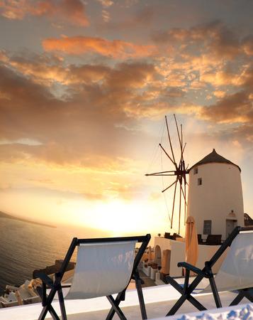 santorini caldera: Windmill against colorful sunset in Santorini, Greece