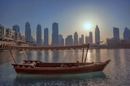 Laguna de Dubai con el barco contra la puesta de sol en Emiratos Árabes Unidos Foto de archivo