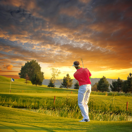 golf man: Man playing golf against colorful sunset