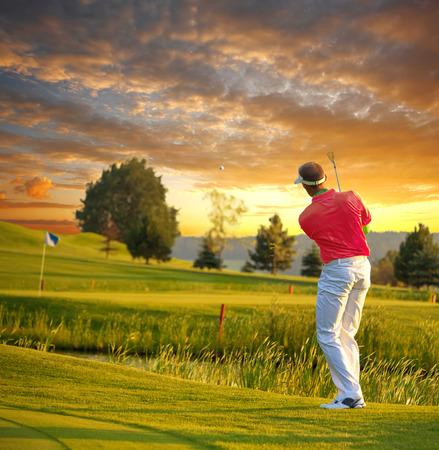 Człowiek gra w golfa przeciwko kolorowe zachód słońca