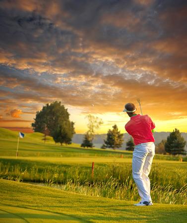 Man spielt Golf gegen farbenprächtigen Sonnenuntergang