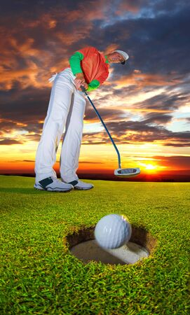 Man playing golf against colorful sunset photo