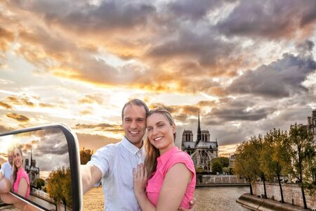 Couple Taking Selfie by famous Notre Dame cathedral in Paris, France photo