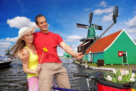 Couple Taking Selfie against famous  windmills in Zaanse Schans, Amsterdam photo