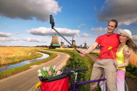 Couple Taking Selfie against famous  windmills in Zaanse Schans, Amsterdam photo