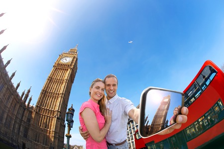 Tourist couple taking selfie against Big Ben in London England UK photo