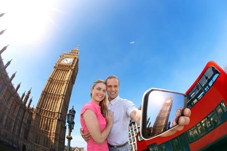 Tourist couple taking selfie against Big Ben in London England UK photo