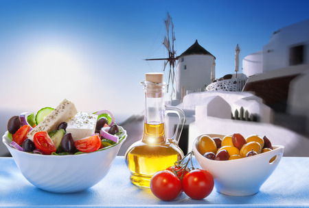 Greek salad against windmill in Oia village Santorini island in Greece