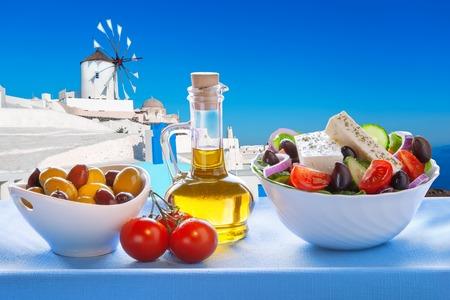 Greek salad against windmill in Oia village Santorini island in Greece