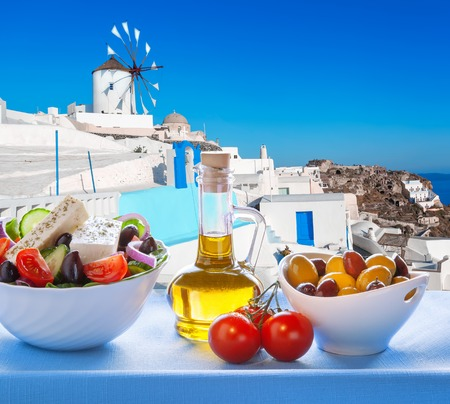 Greek salad against windmill in Oia village Santorini island in Greece photo