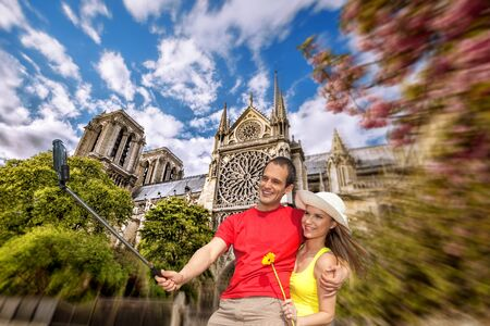 take a history: Couple Taking Selfie the Notre Dame cathedral in Paris France Stock Photo