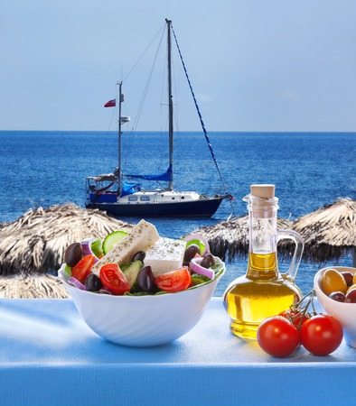 greek salad: Greek salad against sailboat in Santorini island in Greece