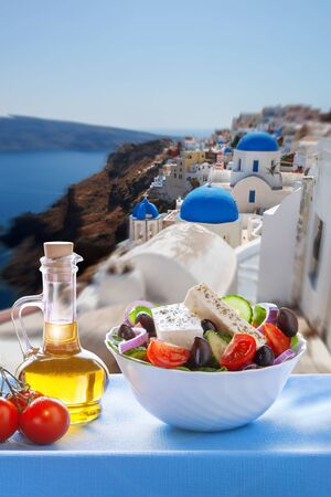 Greek salad against church in Oia village famous Santorini island in Greece