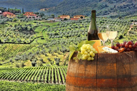 tasting: White wine with barrel on famous vineyard in Chianti Tuscany Italy