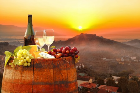 italy landscape: White wine with barrel against colorful sunset famous Chianti in Tuscany Italy Stock Photo