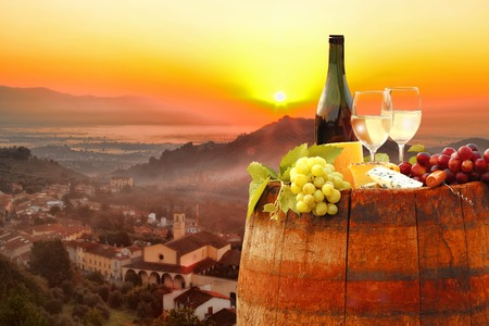 White wine with barrel against colorful sunset famous Chianti in Tuscany Italy Standard-Bild