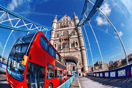double game: Famous Tower Bridge with red bus in London, England