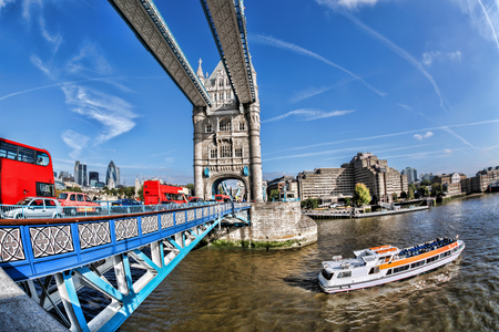 double game: Tower Bridge with red buses and tourist boat in London, England