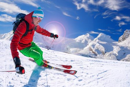 winter vacation: Skier skiing downhill in high mountains, Matterhorn area, Switzerland