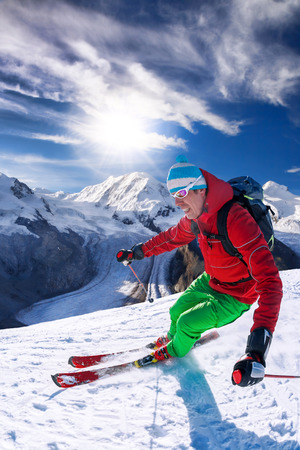 a slope: Skier skiing downhill in high mountains against blue sky