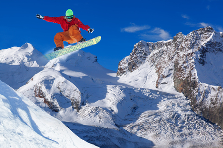 snowboarder jumping: Snowboarder jumping against blue sky Stock Photo