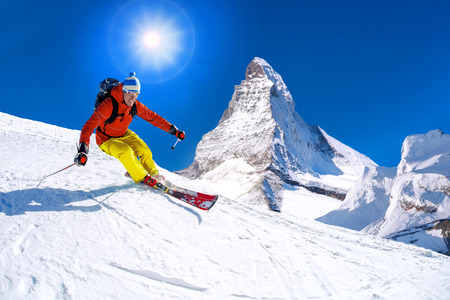 Skier skiing downhill tegen piek Matterhorn in Zwitserland