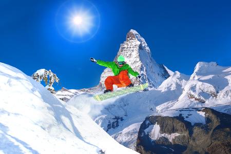 zermatt: Snowboarder jumping against Matterhorn peak in Switzerland