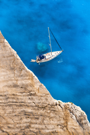 White Luxury Yacht against azure sea with high cliff