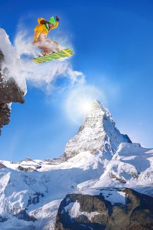 snowboarder jumping: Snowboarder jumping against Matterhorn peak in Switzerland