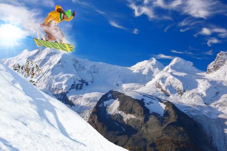 zermatt: Snowboarder jumping against blue sky Stock Photo