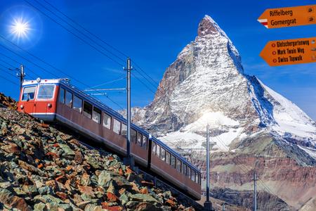 Signpost against Matterhorn with train from Zermatt in the Swiss Alps Foto de archivo