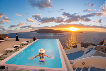 Woman in the swimming pool against sunset in Oia village on Santorini island, Greece Stock Photo