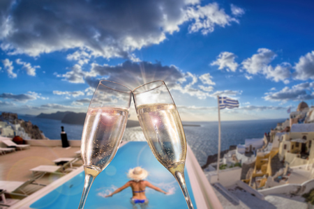 boat party: Glasses of wine with woman in swimming pool on Santorini island, Greece