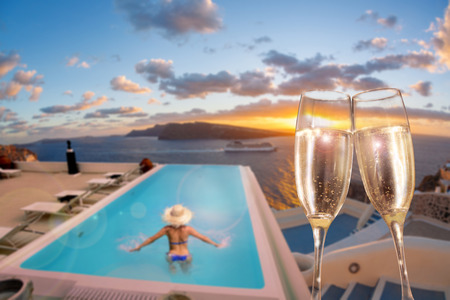 Glasses of wine with woman in swimming pool on Santorini island, Greece