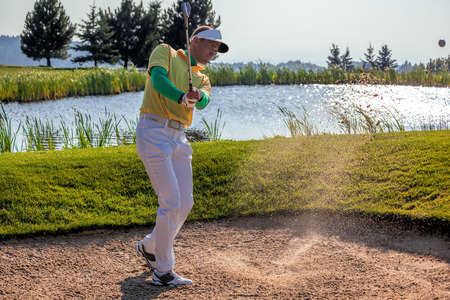 Man playing golf from the bunker