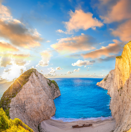 sunrise ocean: Navagio beach with shipwreck against colorful sunset on Zakynthos island in Greece Stock Photo