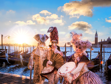 Venedig mit Karnevalsmasken gegen bunte Sonnenaufgang in Italien