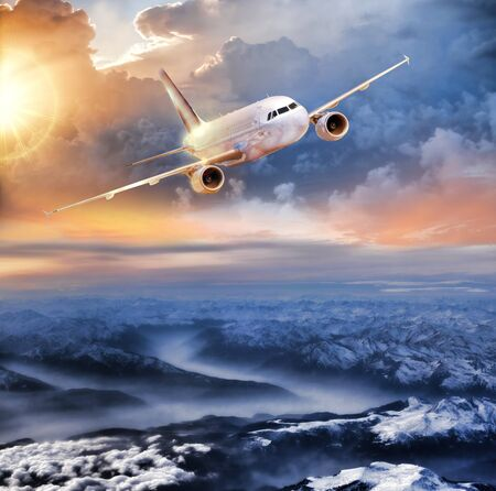 high class: Airplane in the sky over winter Alps at amazing colorful sunset