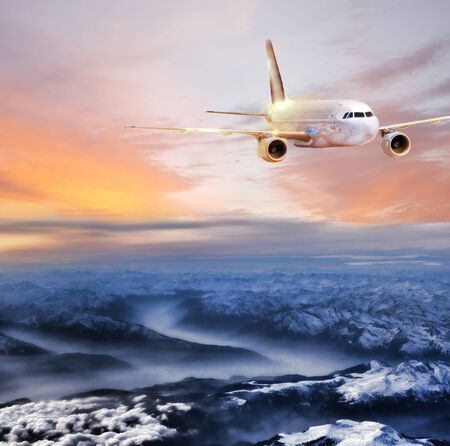 air travel: Airplane in the sky over winter Alps at amazing colorful sunset