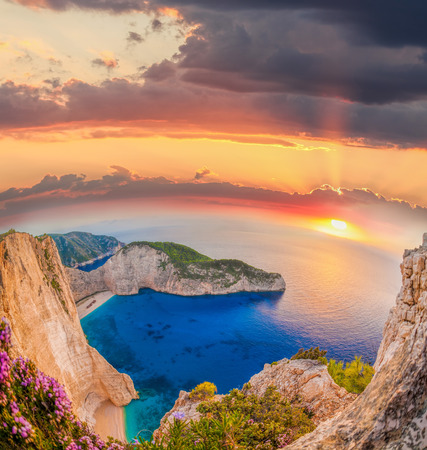 ionian island: Navagio beach with shipwreck and flowers against sunset on Zakynthos island in Greece