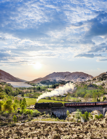 jacobite: Glenfinnan Railway Viaduct in Scotland with the Jacobite steam train against sunset over lake