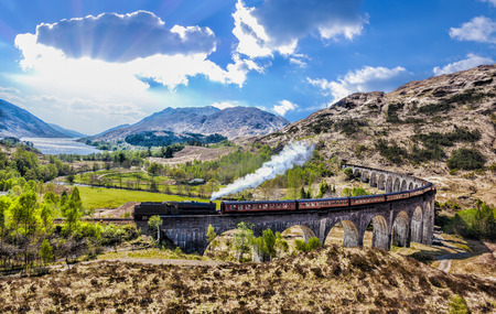 Glenfinnan Railway Viaduct in Scotland with the Jacobite steam train against sunset over lake Zdjęcie Seryjne - 57170009